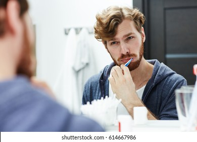 Young man brushing his teeth in bathroom