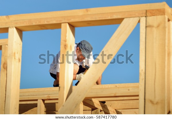 The young man, a builder builds a wooden frame house in the summer on a background of blue sky
