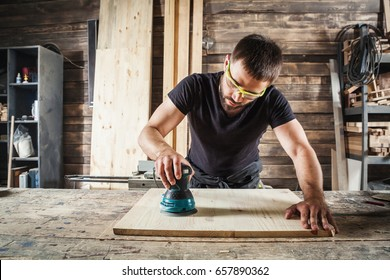 Young man builder carpenter equals polishes wooden board with a  random orbit sander  in the workshop