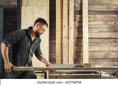 Young man builder carpenter sawing board with circular saw in workshop
