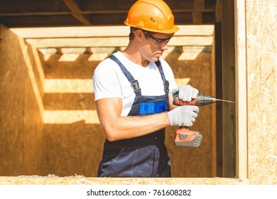 Young man building wooden house. Ecology concept.