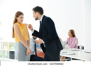 Young man bullying his colleague at work