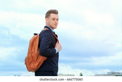 Young man in a business suit and with a backpack behind him after a hard day's work. Life style of modern man.