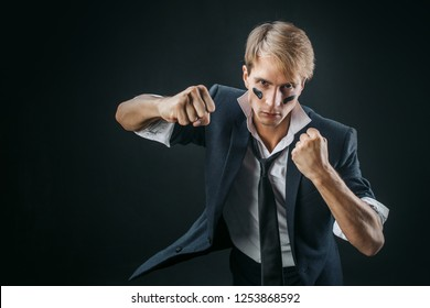 A young man in a business suit rolled up his sleeves and Boxing. Aggressive business, concept. Businessman with war paint on his face
