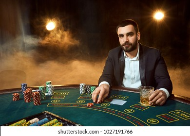 A young man in a business suit sitting at the poker table. Man gambles. The player at the gaming table playing cards.