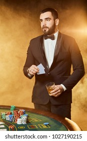A young man in a business suit standing near poker table. Man gambles.