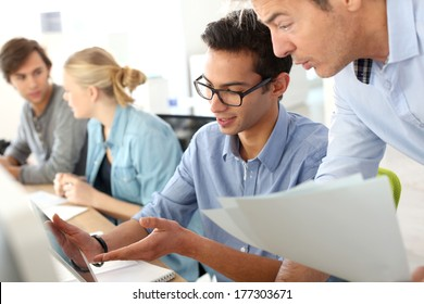 Young man in business training school with teacher