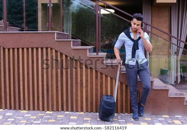 Young man businessman Arabian beautiful appearance is black travel bag on small wheels and is waiting for taxi, on journey or business trip, using phone and check their seats in airplane online
