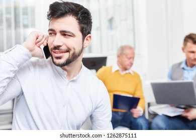 Young man as businessman calling with smartphone and listening