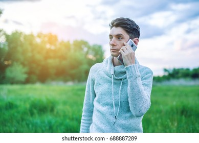 Young man businessman talking at mobile phone outside on a grass field at sunset