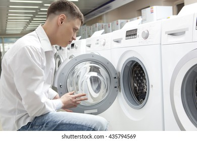 Young man buying new washing machine in store