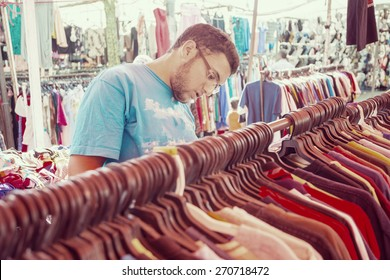 Young man buying in second hand store