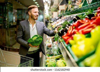 Young man buying vegetables in the supermarket