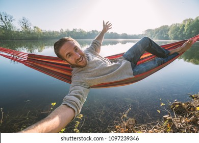 Young man by the lake hanging on hammock relaxing in the morning takes a selfie portrait. People relaxation travel concept.