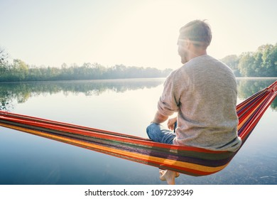 Young man by the lake hanging on hammock relaxing in the morning. People relaxation travel concept.