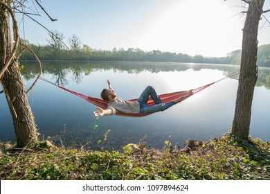 Young man by the lake hanging on hammock relaxing in the morning and stretching arms outstretched . People relaxation travel concept.