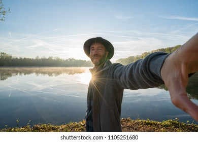 Young man by the lake at sunrise takes a selfie portrait using mobile phone, beautiful reflection on water surface. Travel people concept France