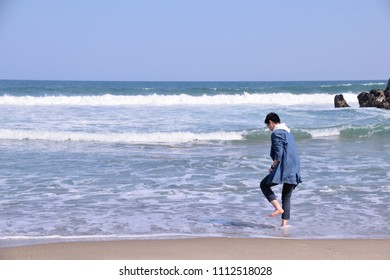 A young man by the waviness. Background,coast,blue,wave.