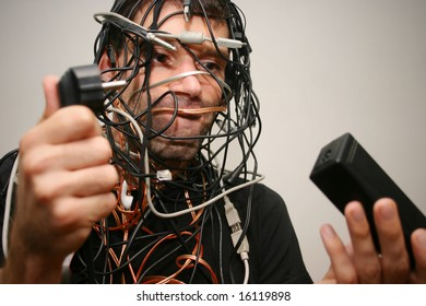 young man in cable chaos with difficulties finding the right connection