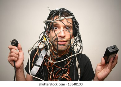 young man in cable chaos with wrong plugs