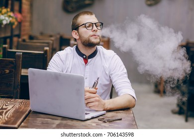 young man in cafe with laptop and electronic cigarette