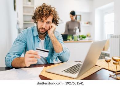 Young man calculating bills to pay with credit card while woman cooking in kitchen