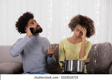 Young Man Calling Plumber While Woman Using Utensil For Collecting Water Leaking From Ceiling