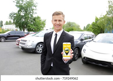 Young man calling taxi by cellphone outdoors