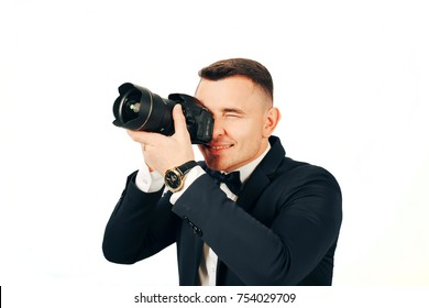 A young man with a camera in hands takes pictures on a white background
