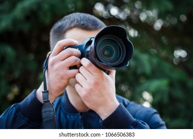 A young man with a camera takes pictures of nature