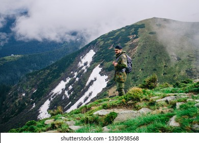 A young man in camouflage and a backpack in the mountains