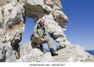 Young man in camouflage uniforms sits on the edge of a rock