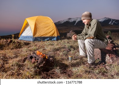 Young Man Camping and Enjoying the Fire