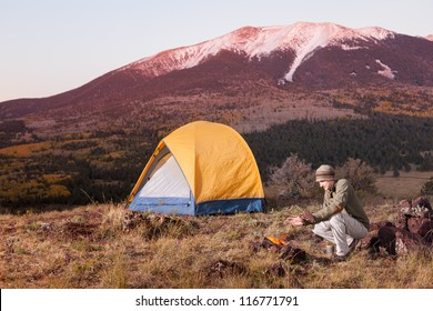 Young Man Camping and Keeping Warm by Fire
