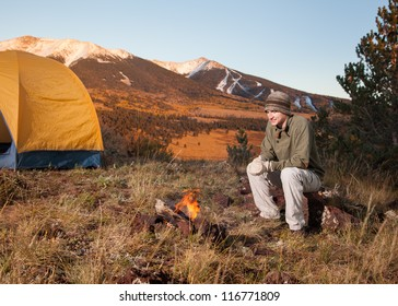 Young Man Camping and Sitting Next to Fire
