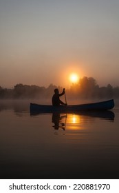 Young man canoeing in Canada at dawn