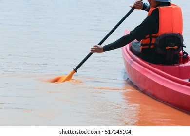 Young man canoeing on red river.Adventure travel canoeing in a lake on a summer day.