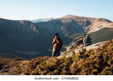Young man in cap and sunglasses with a backpack walks the trail at the top of the mountain. Mountain hike in the sunny Carpathians. Hiking concept.