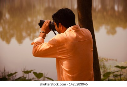 Young man capturing photos with a DSLR camera unique photo