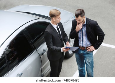 Young man with car dealer outdoors