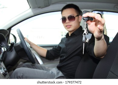 A young man in a car holding up / handing over the car keys. Focus is on the keys