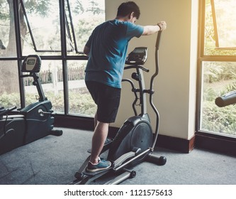Young man cardio workout in gym,elliptic in fitness center.