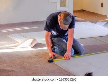 Young man carpenter measuring new rugs he's going to install in house; sunlight coming from the windows