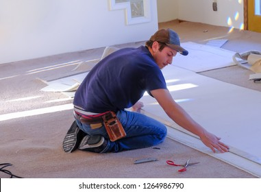 Young man carpenter  measuring pieces of rug he's laying in house; sunlight coming from to room