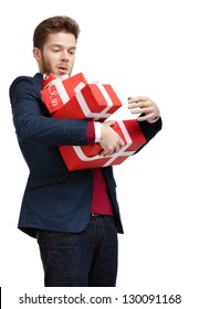 Young man carries a great amount of presents wrapped in red gift paper, isolated on white