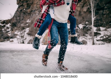Young man carries his girlfriend on back across puddle of melted water with flying apart water splashes.