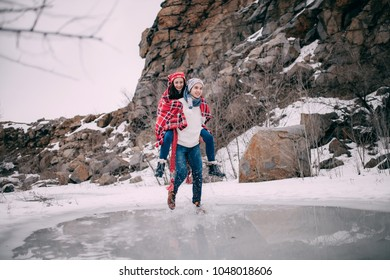 Young man carries his girlfriend on back across puddle of melted water with flying apart water splashes. Couple laughs.