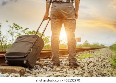 A young man carries a suitcase waiting for a train