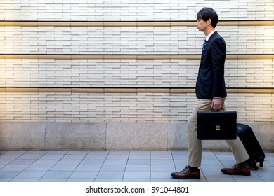 young man carrying a carry bag with him on passage of modern building