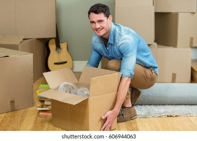 Young man carrying carton boxes in his new house